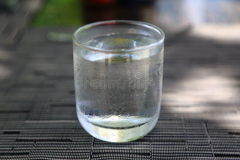 Exponeringsglas av kallt vatten på grå färger bryner bakgrund på en varm sommardag Temperaturkontrast royaltyfri fotografi