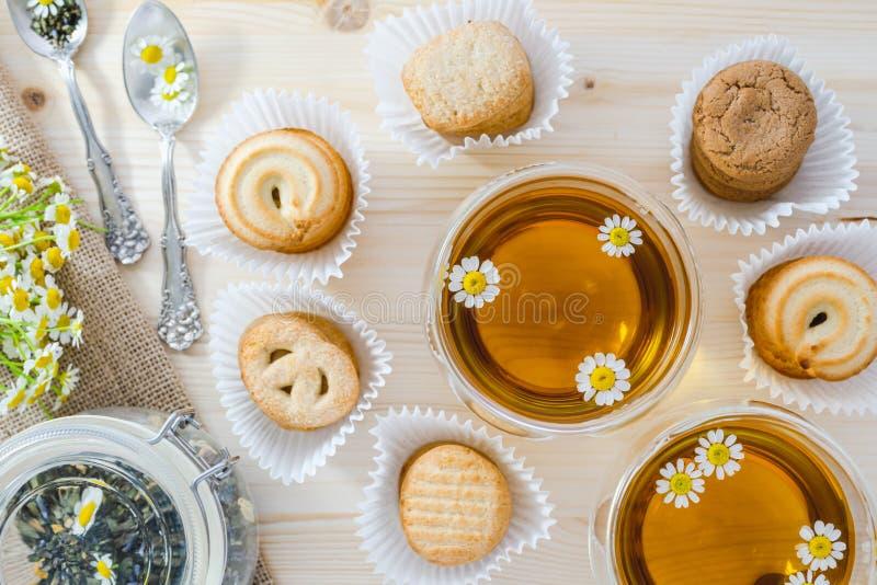 Exponeringsglas av kamomillte och kakor p? ett tr?k?ksbord, slut upp, b?sta sikt fotografering för bildbyråer