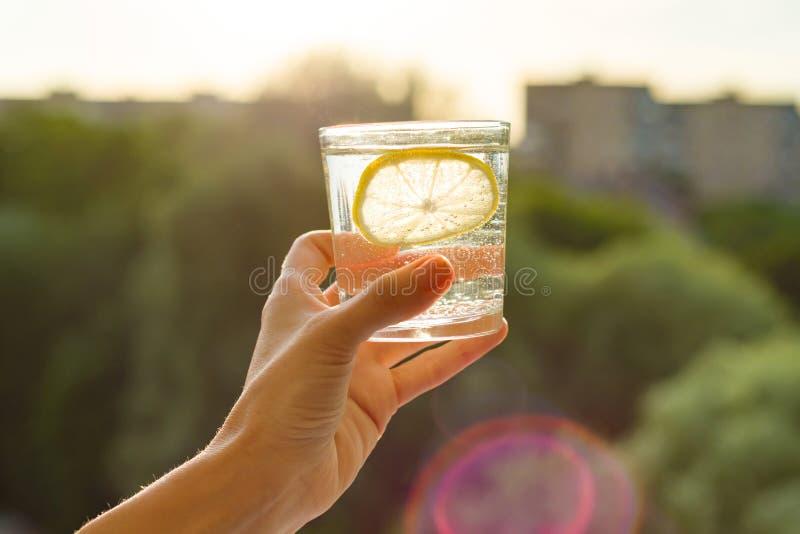 Exponeringsglas av klart, kolsyrat vatten med citronen i hand Bakgrundshimmel, kontur av staden, solnedgång arkivfoto