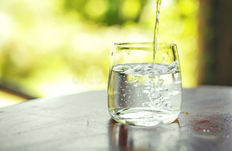 Exponeringsglas av klart vatten på tabellen royaltyfria bilder