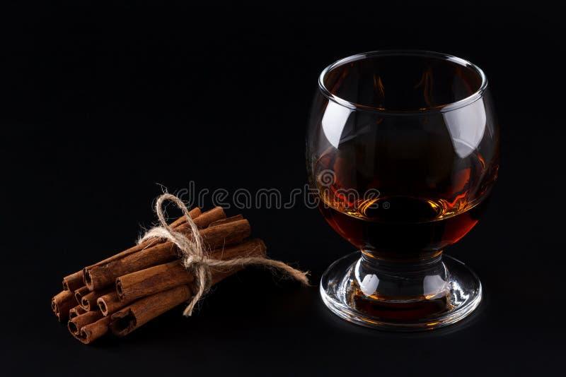 Exponeringsglas av konjak- eller mörkerrom och kanelbruna pinnar på svart bakgrund royaltyfri foto