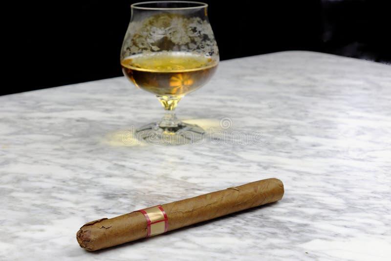 Exponeringsglas av konjak med en cigarr på en marmortabell royaltyfri foto