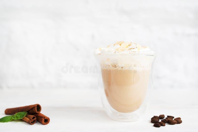 Exponeringsglas av latte med kanel- och kaffebönor royaltyfria bilder