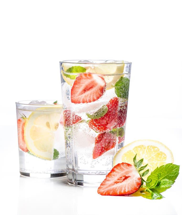 Exponeringsglas av lemonad med citronen, limefrukt och mintkaramellen på vit bakgrund royaltyfri bild