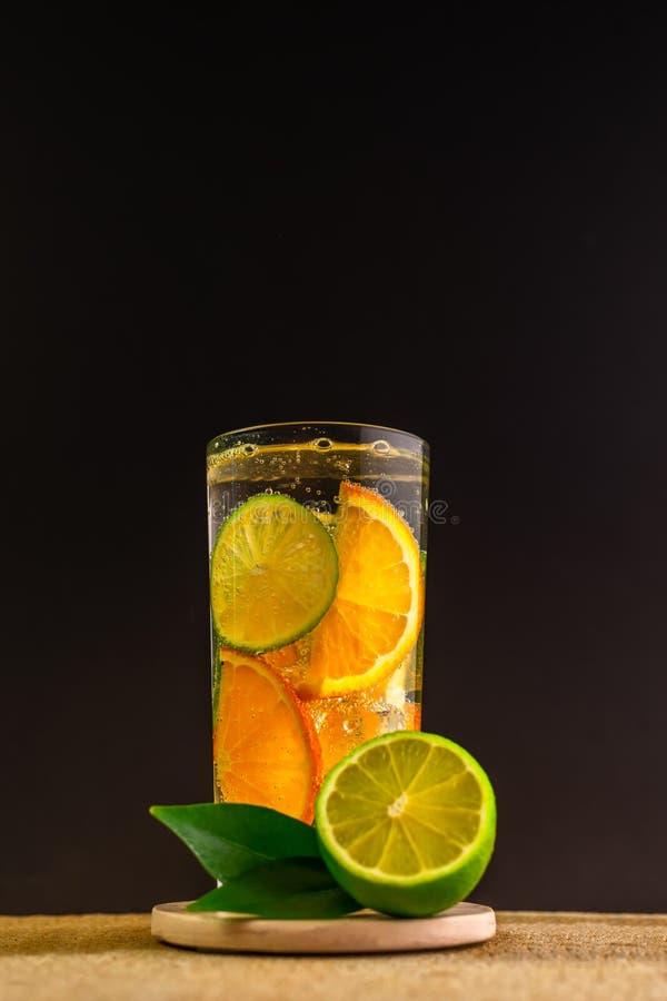 Exponeringsglas av lemonad med mineraliskt ingett detoxvatten med apelsinen, limefrukt dekorerade frukter på stenbakgrund över sv arkivfoto