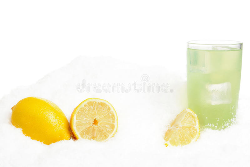 Exponeringsglas av limefruktfruktsaft med iskuber, citroner på snö på vit royaltyfri bild