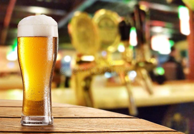 Exponeringsglas av ljus öl på en mörk pub arkivfoto