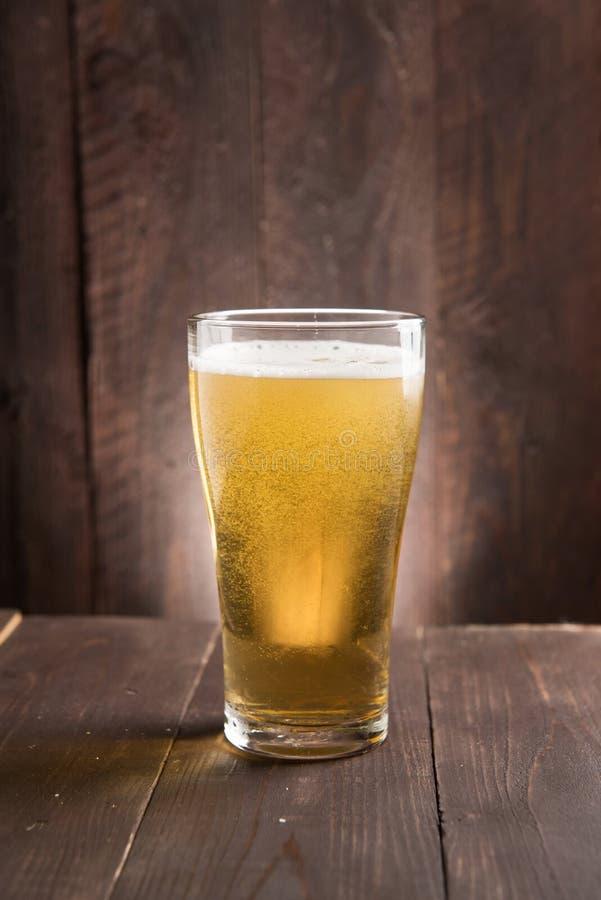 Exponeringsglas av ljust öl på träbakgrund royaltyfri fotografi