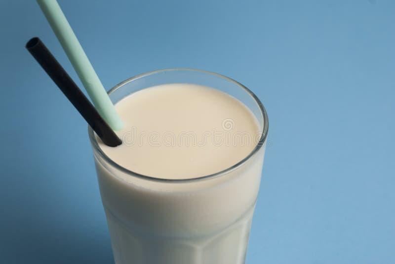 Exponeringsglas av mjölkar den Straw Isolated Blue Background Lactose mejeriprodukten royaltyfri foto