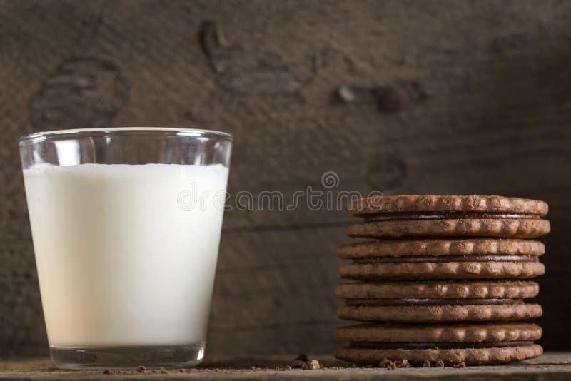 Exponeringsglas av mjölkar och chokladkex på trätabellen arkivbilder