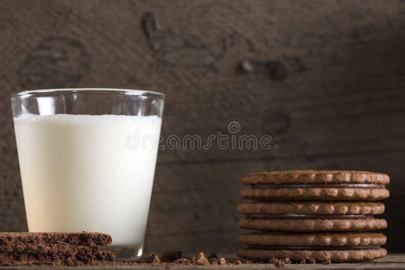 Exponeringsglas av mjölkar och chokladkex på trätabellen arkivfoto