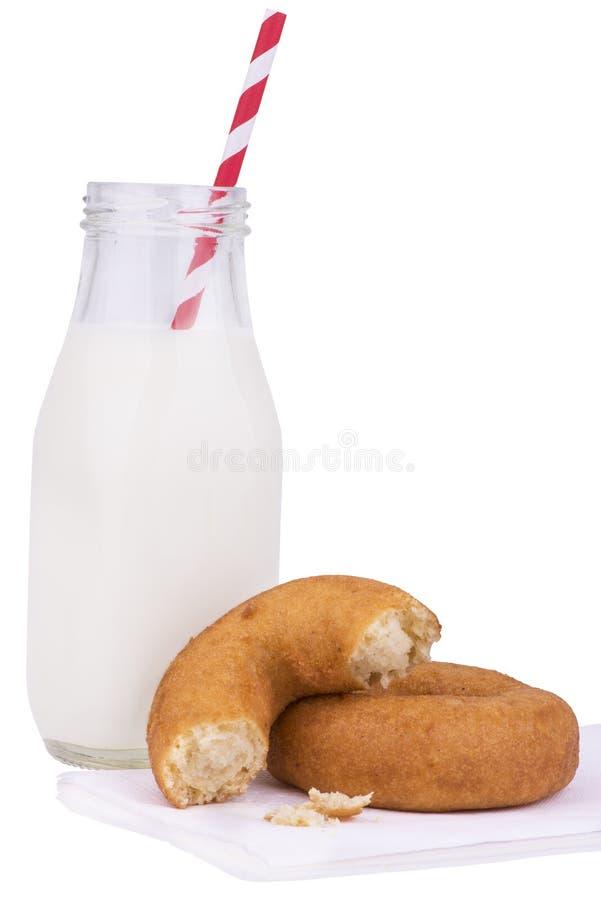 Exponeringsglas av mjölkar och donuts royaltyfri fotografi