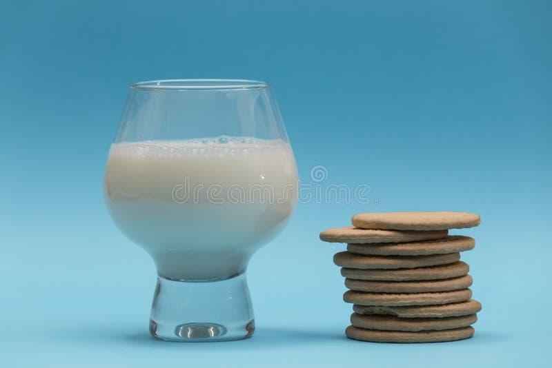 Exponeringsglas av mjölkar och gruppen av kakor på blå bakgrund royaltyfria foton