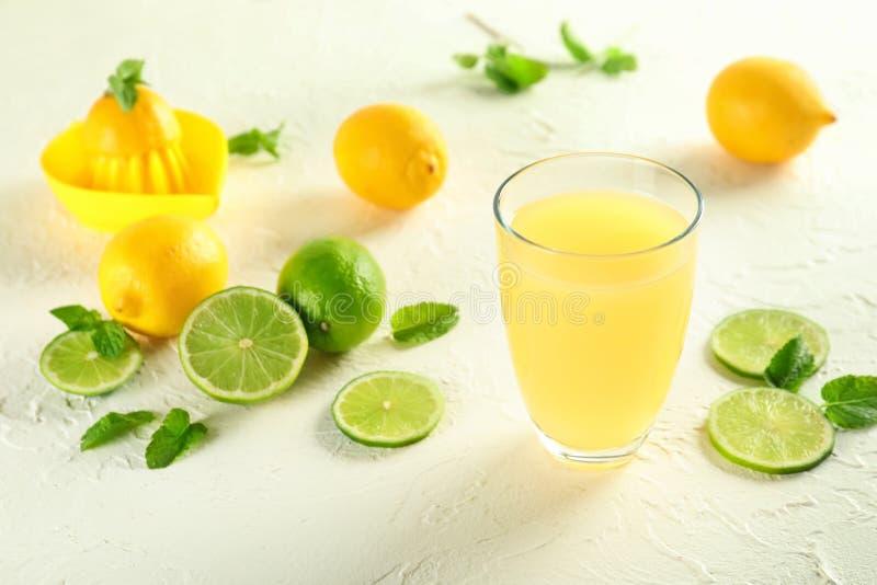 Exponeringsglas av ny citronjuice och skivor av limefrukt på vit texturerad bakgrund arkivbilder