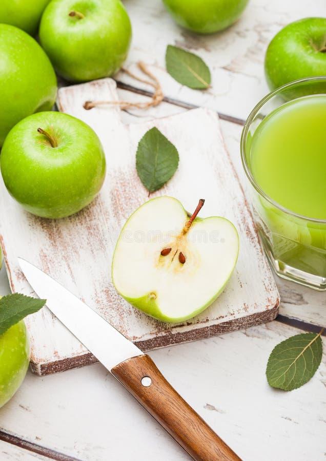 Exponeringsglas av ny organisk äppelmust med gröna äpplen på träbakgrund med kniven arkivfoto