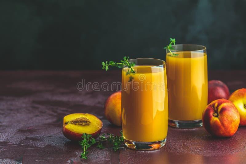 Exponeringsglas av ny sund persikasmoothie eller fruktsaft royaltyfri bild