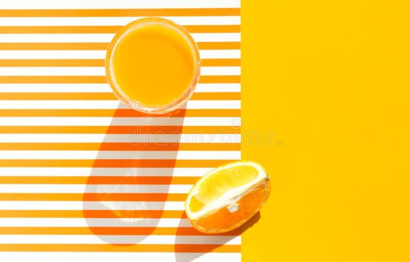 Exponeringsglas av nytt sammanpressad orange fruktsaft med trämassafruktkilen på gul för duotone ljus solig och vit randig bakgru royaltyfria bilder