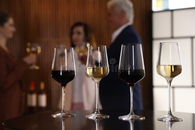 Exponeringsglas av olika viner på tabellen mot gjort suddig arkivbild