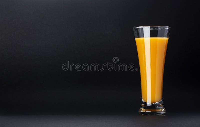 Exponeringsglas av orange fruktsaft som isoleras på svart bakgrund med kopieringsutrymme för text, ny citrus coctail royaltyfri foto