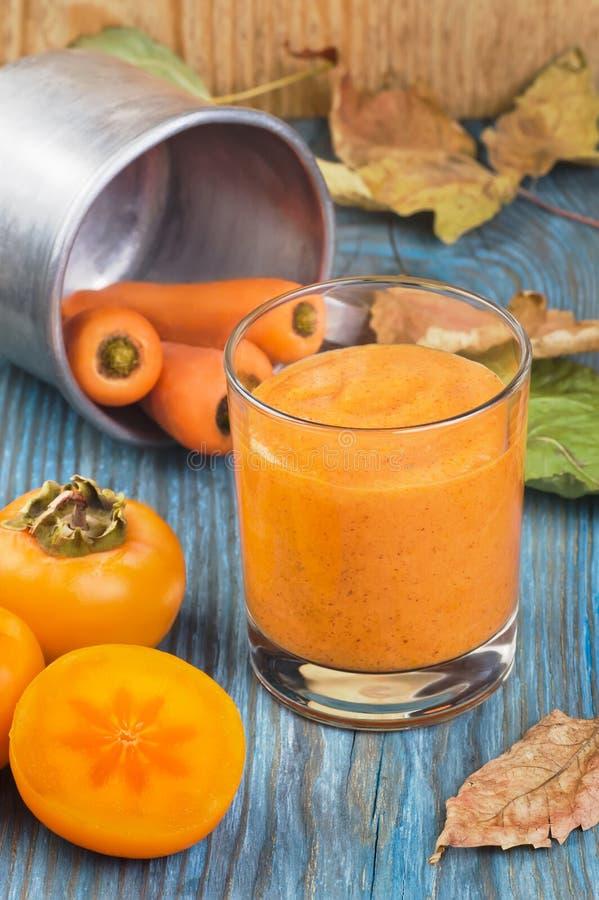 Exponeringsglas av persimonsmoothien med smaksatt kanel för morotfruktsaft som dekoreras av ingredienser och stupade sidor på blå royaltyfri bild