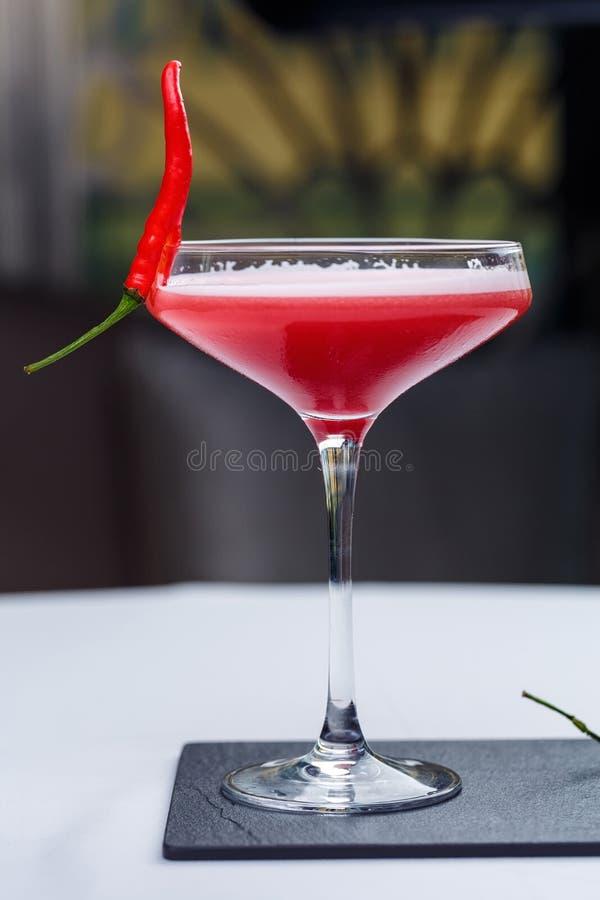 Exponeringsglas av röda martini dekorerade med chilipeppar arkivbilder