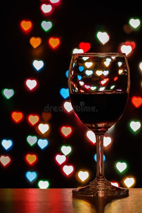 Exponeringsglas av rött för vin med suddig ljus hjärta arkivfoton
