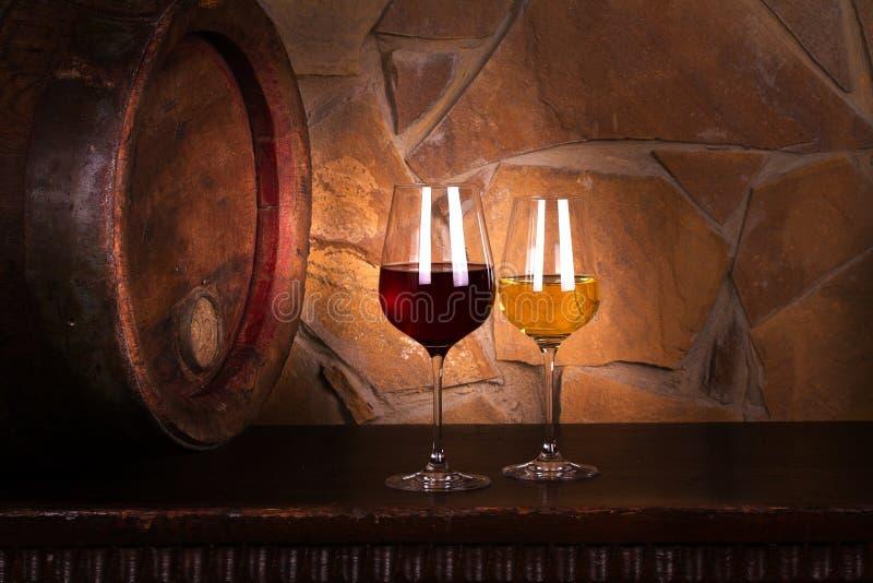 Exponeringsglas av rött och vitt vin i vinkällaren, gammal vinfat arkivfoto