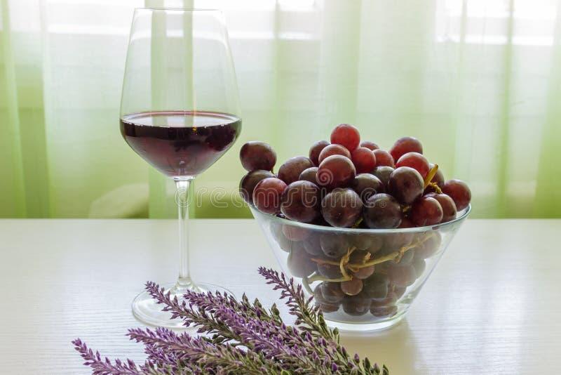 Exponeringsglas av rött vin, druvor och lavendel på den vita trätabellen royaltyfria foton