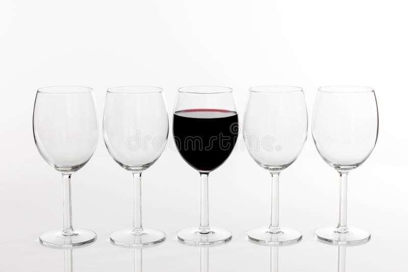 Exponeringsglas av rött vin i rad av tomma exponeringsglas royaltyfria bilder