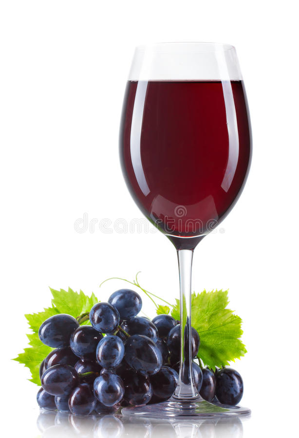 Exponeringsglas av rött vin med den isolerade flaskan och mogna druvor arkivbild