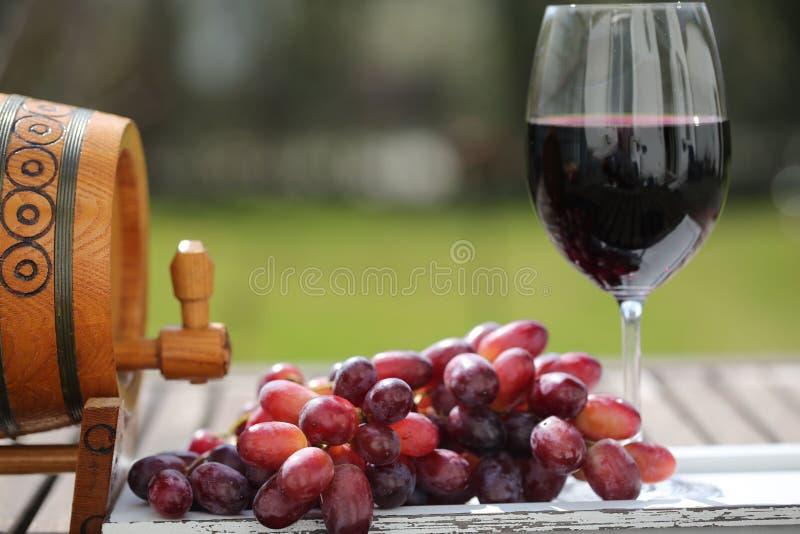 Exponeringsglas av rött vin med druvor på trätabellen royaltyfria bilder