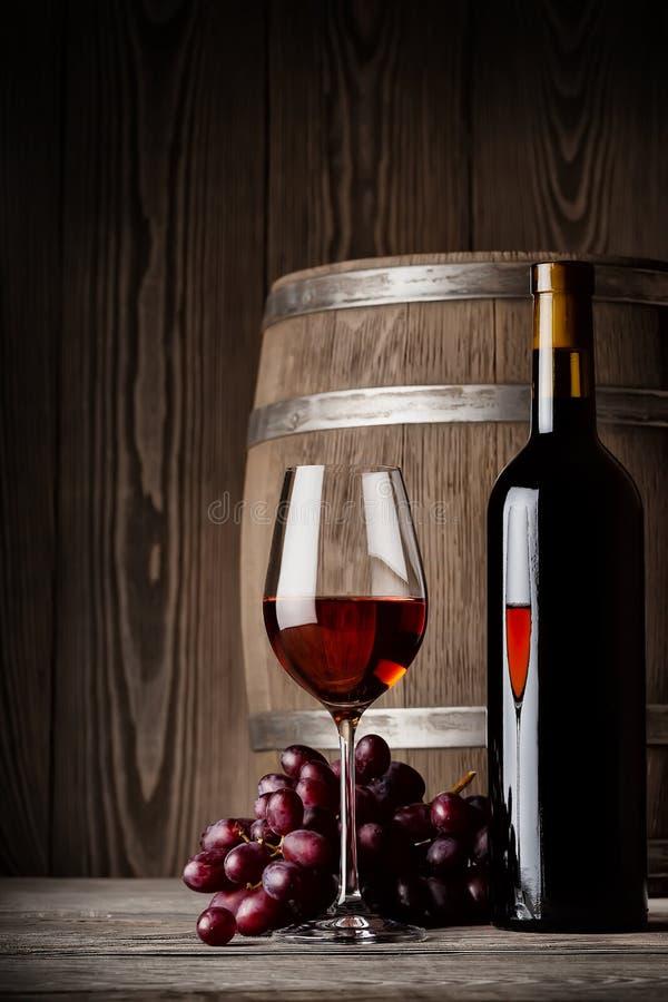 Exponeringsglas av rött vin med flask- och kaggeanseende royaltyfri foto