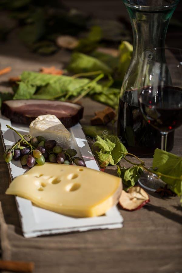 Exponeringsglas av rött vin, med karaffen, ost och druvor fotografering för bildbyråer