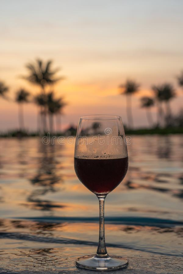 Exponeringsglas av rött vin med simbassängbakgrund arkivfoton