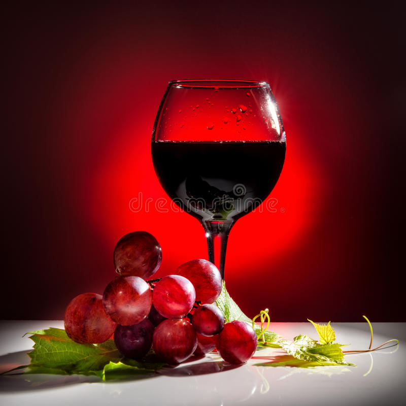 exponeringsglas av rött vin och vinrankan med det gröna bladet royaltyfria bilder