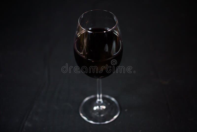 Exponeringsglas av rött vin på en svart bakgrund arkivfoto