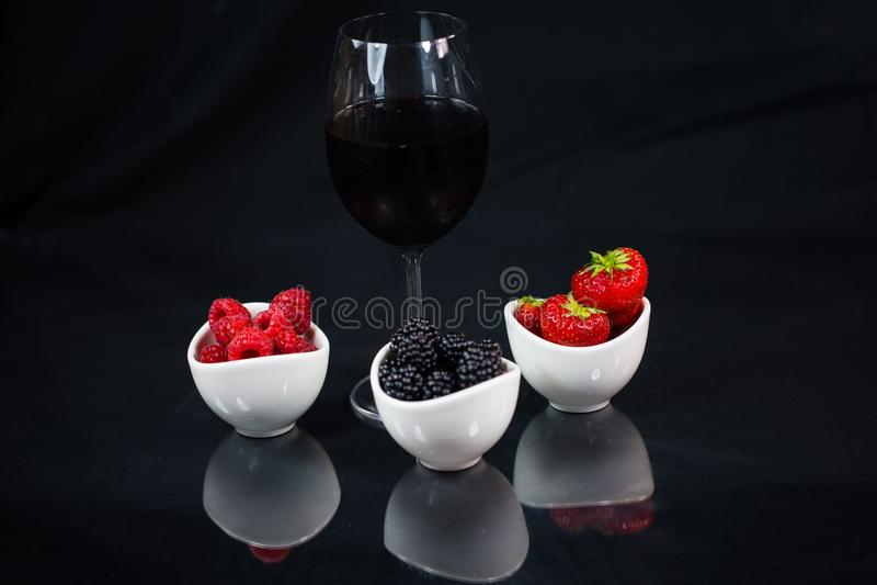 Exponeringsglas av rött vin på en svart bakgrund med jordgubbar, svart arkivbild