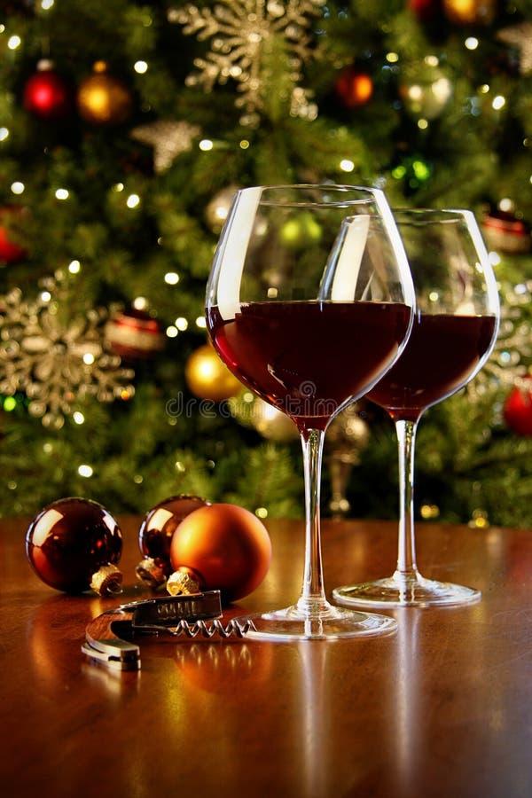 Exponeringsglas av rött vin på tabellen med julgranen arkivfoton