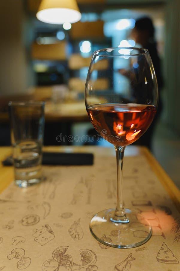 Exponeringsglas av rosa vin på tabellen arkivbilder