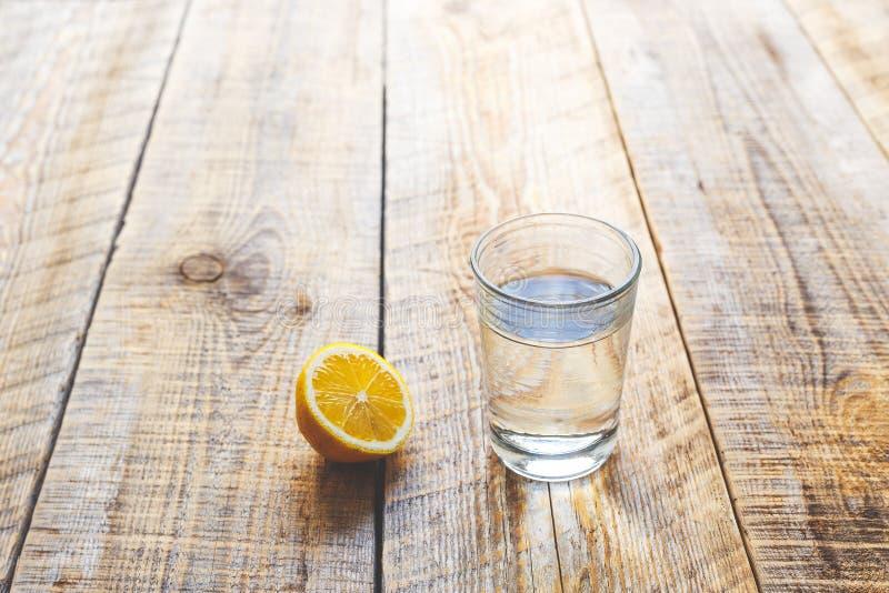 Exponeringsglas av sötvatten med den halva citronen på trätabellen arkivbilder