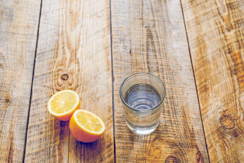 Exponeringsglas av sötvatten med den halva citronen på trätabellen arkivfoto