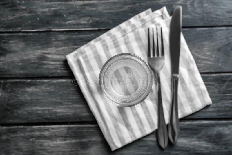 Exponeringsglas av sötvatten med gaffeln och kniven på trätabellen royaltyfria foton