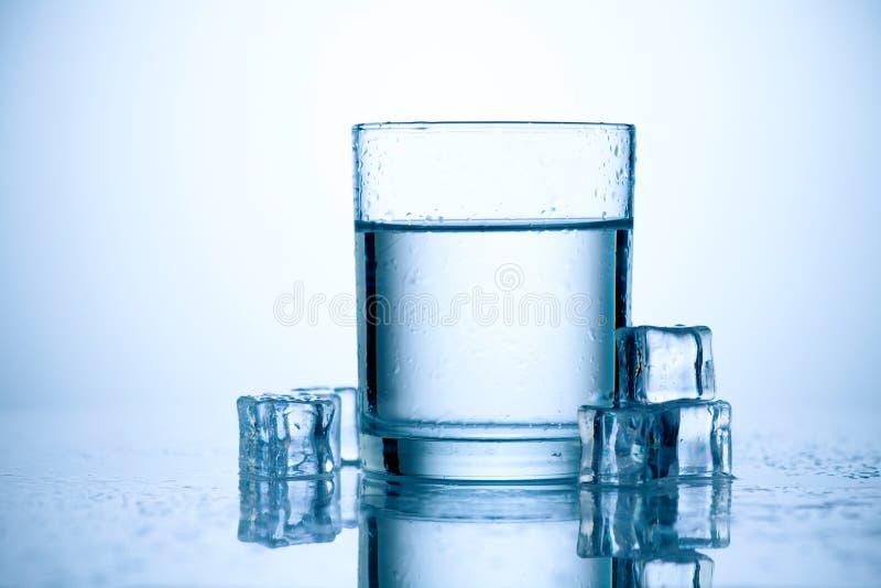 Exponeringsglas av sötvatten med iskuber royaltyfri bild