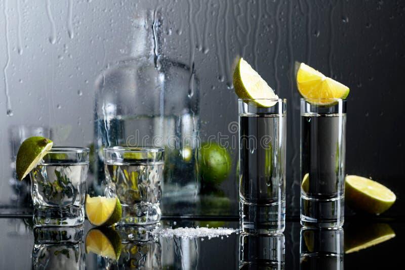 Exponeringsglas av tequila med limefrukt och att salta på den svarta reflekterande bakgrunden fotografering för bildbyråer