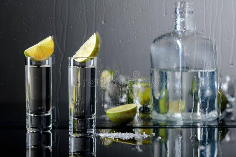 Exponeringsglas av tequila med limefrukt och att salta på den svarta reflekterande bakgrunden royaltyfri foto