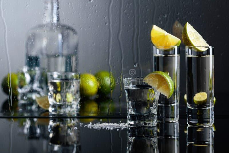 Exponeringsglas av tequila med limefrukt och att salta på den svarta reflekterande bakgrunden arkivfoto