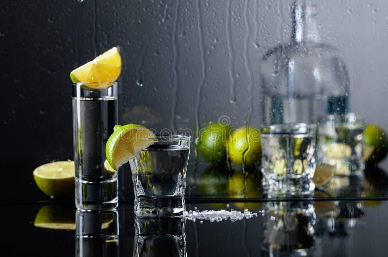 Exponeringsglas av tequila med limefrukt och att salta på den svarta reflekterande bakgrunden arkivbilder