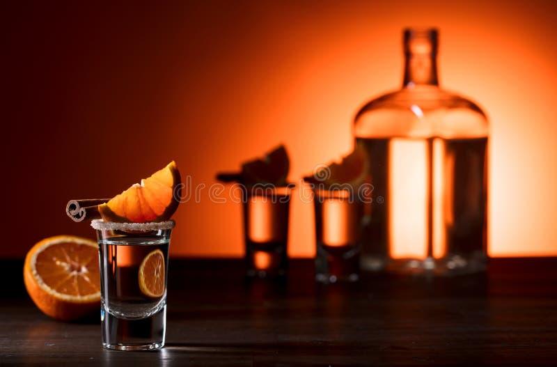 Exponeringsglas av tequila med orange och kanelbruna pinnar arkivbilder