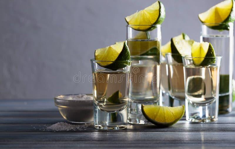 exponeringsglas av tequila- och limefruktskivor arkivbild