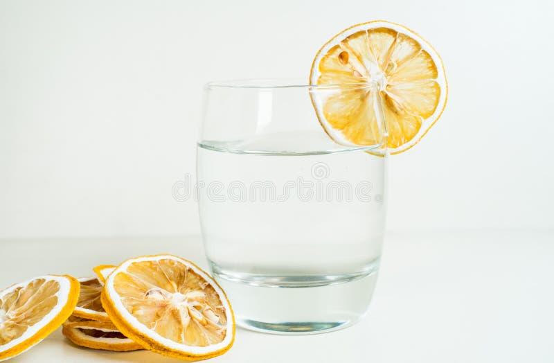 Exponeringsglas av torkade citronskivan för vatten den garnering i vit bakgrund royaltyfria foton